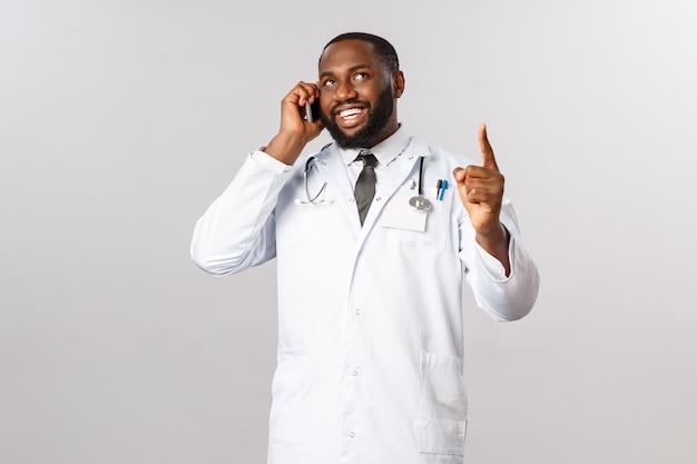 Концепция пандемии и онлайн-медицины. профессиональный красивый афро-американский врач консультирует пациента по телефону во время улыбающегося звонка клиенту, назначает лечение