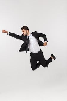 Молодой счастливый кавказский бизнесмен скача и летая в воздух, изолированный на белой стене