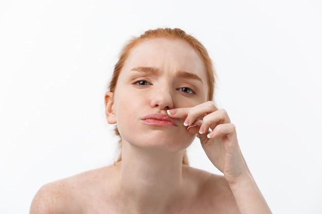 若い白人女性は美しさの顔ににきびを絞る