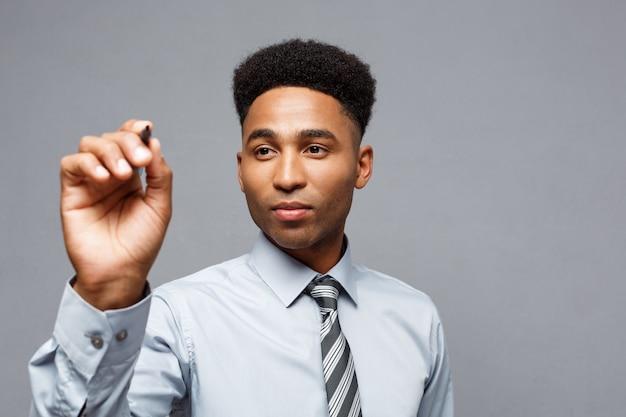 自信を持ってアフリカ系アメリカ人のビジネスマネージャーは、オフィスで仮想ボードまたはガラスに書く準備をしました。