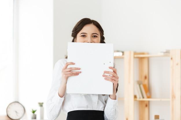 Молодая женщина с удивленными глазами, выглядывающими из-за бумажного плаката. коммерсантка держа большое белое знамя в современном офисе.