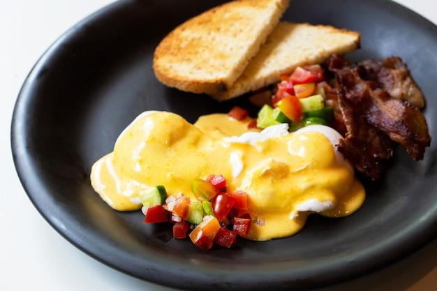 エッグベネディクト-パン、ベーコンとトマト、ポーチドエッグ、そしておいしいバターのオランデーズソース