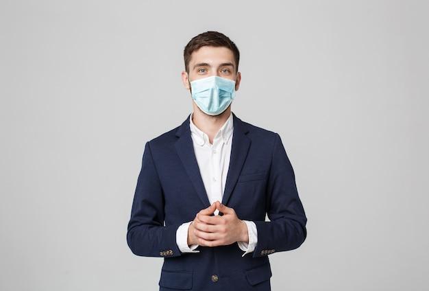 事業コンセプト-自信を持って顔と手を繋いでいるフェイスマスクの肖像画ハンサムなビジネスマン。白い壁。