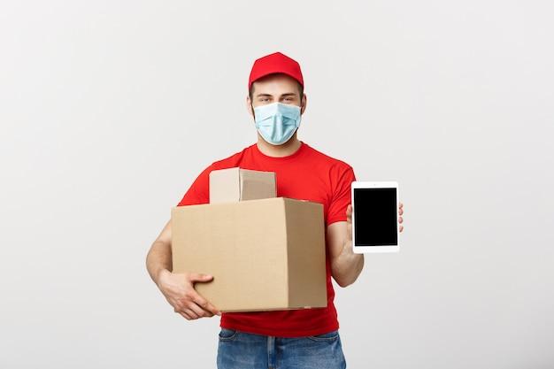 オンラインショッピング、配送、技術、ライフスタイルのコンセプト-タブレットを提示し、彼の手でボックスを保持している配達人の笑顔。白いスタジオの壁に分離。