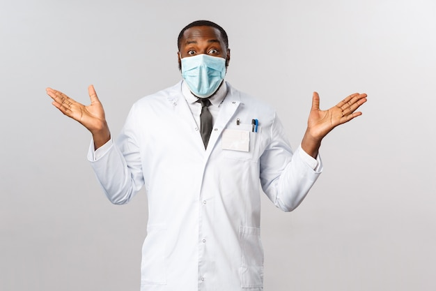 おめでとう、治った。白衣を着た笑顔のアフリカ系アメリカ人男性医師の幸せと安堵の肖像画、手を喜んで横に広げ、驚いて見て、患者が元気になる