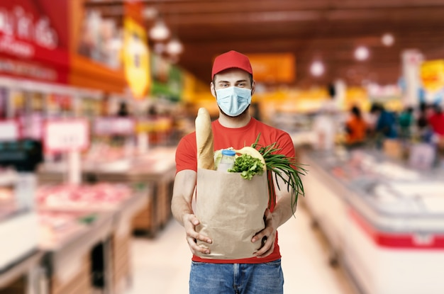 Работник доставочной компании держит продуктовый ящик, заказ еды, услуги супермаркета