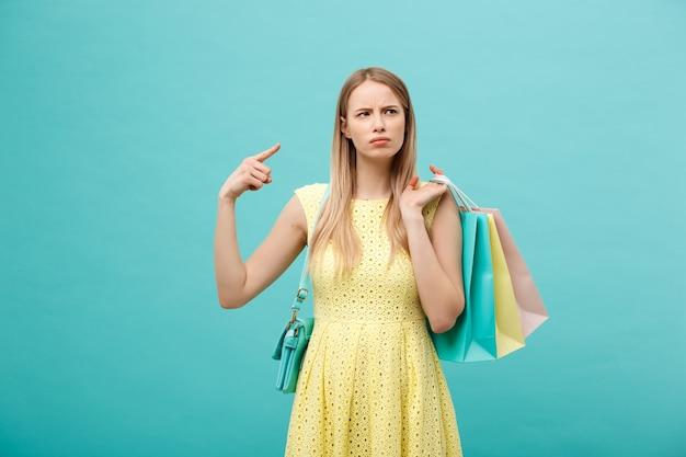 Концепция покупки и продажи: красивая несчастная молодая женщина в желтом элегантном платье с хозяйственной сумкой.
