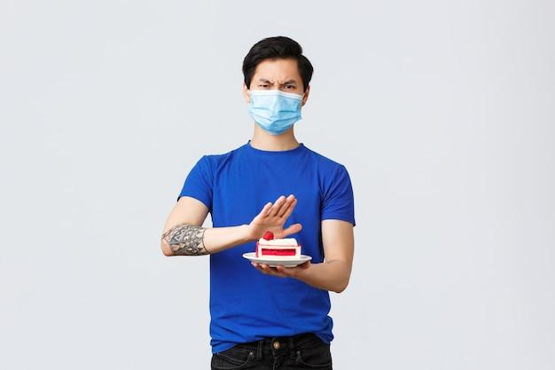 Самостоятельный карантин, домашний образ жизни и концепция празднования. злой противный молодой азиатский парень не любит десерт, отвергая ужасный отвратительный пирог, нахмурившись разочарован, надев медицинскую маску