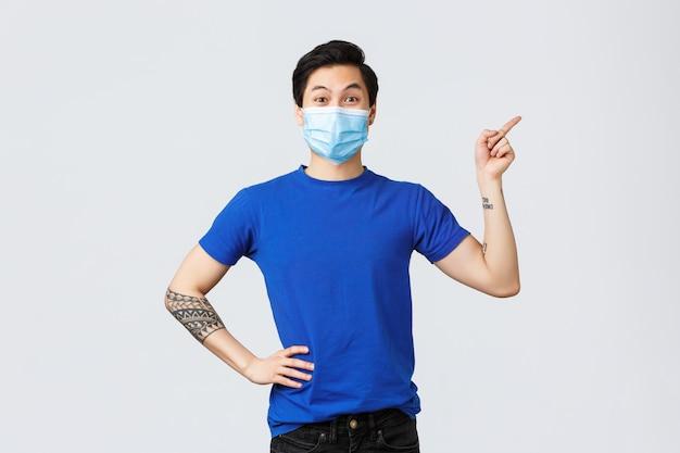 コロナウイルスとライフスタイルのコンセプト。医療マスクの熱狂的なアジアの男性は、偉大な新しいプロモーション、特別割引、右向きを知らせます