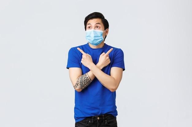 Коронавирус и концепция образа жизни. нерешительный и растерянный азиатский мужчина в медицинской маске, указывая влево и вправо, двумя способами, не может решить несколько вариантов