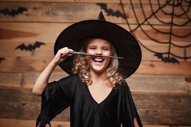 ハロウィーンの魔法の概念 - 小さな魔女の子供は魔法の棒で遊ぶことを楽しむ。バットとスパイダーウェブの背景。