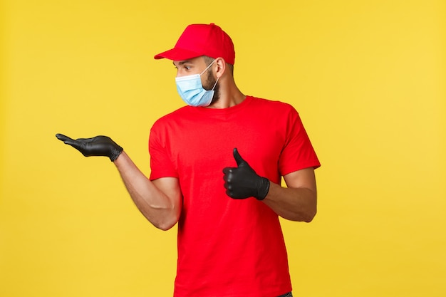 感動した宅配便、赤い制服を着た従業員と医療マスク、彼の手を見て親指を立てる