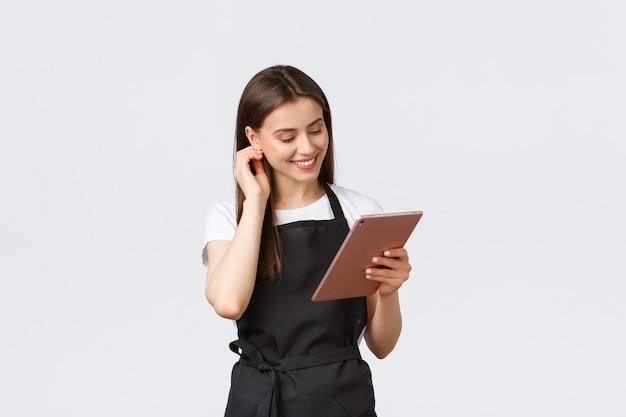 食料品店の従業員、中小企業、コーヒーショップのコンセプトです。カフェの注文を管理するためにデジタルタブレットを使用して、カメラに笑顔の黒のエプロンでフレンドリーなかわいい女性バリスタ