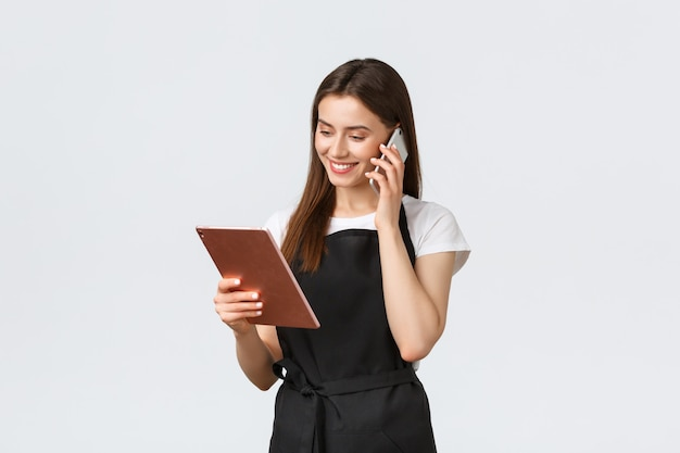 食料品店の従業員、中小企業、コーヒーショップのコンセプトです。黒のエプロンでかわいい笑顔の店員が注文を確認し、電話でお客様と話し、デジタルタブレットを見て