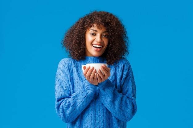 幸福、快適さ、居心地の良い家のコンセプト。幸せなリラックスして陽気なアフリカ系アメリカ人女性が素敵なホットカップティーを楽しんで、笑顔で見つめて喜んで、青い壁に満足して立っています。