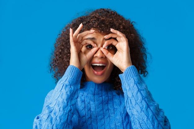 双眼鏡を押しながら印象的な素晴らしいプロモーションをチェックしたり、笑って楽しんだりするような、大丈夫なジェスチャーを見て、驚いて魅了され、興奮したアフリカ系アメリカ人の女性
