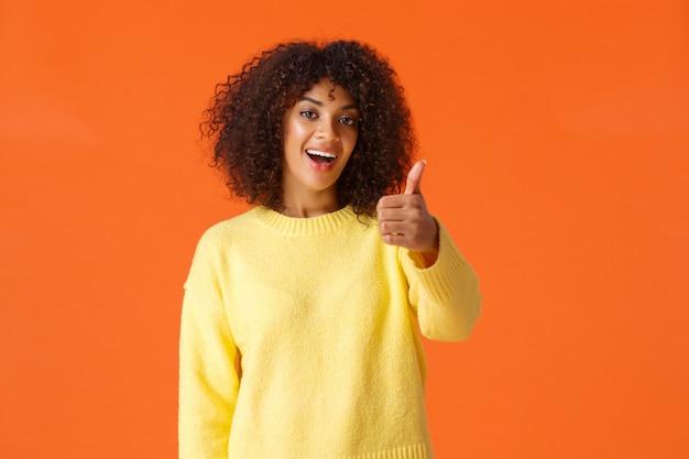 巻き毛の陽気な発信現代アフリカ系アメリカ人女性、いいね、承認、または応援ジェスチャーで親指を立てる