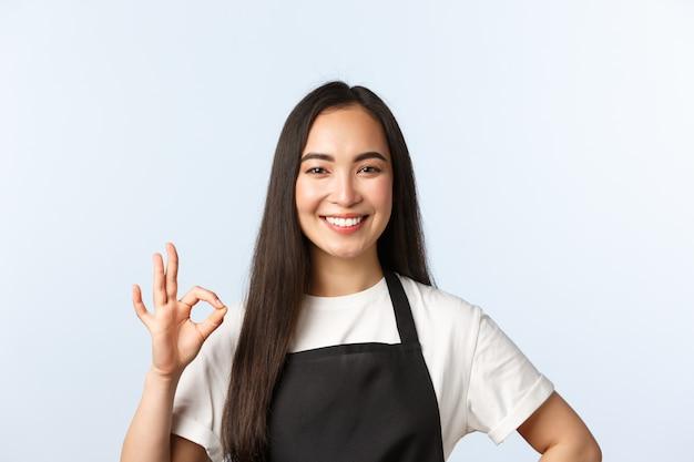 コーヒーショップ、スモールビジネス、スタートアップのコンセプト。快適なかわいい笑顔のアジアのバリスタ、黒いエプロンの店またはカフェの従業員は、サービスの品質を保証し、大丈夫な標識を示し、場所をお勧めします