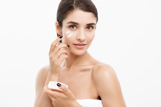 美容ユーススキンケアコンセプト - クローズアップ美しい白人女性の顔の肖像画スキンケアのための彼女の顔にいくつかのクリームを適用します。美しいスパモデルのガールズ、白い背景の上に完全なきれいな肌を持つ少女。