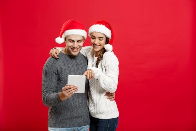 Молодая красивая и красивая пара пользуются играть на планшете в рождественский день.