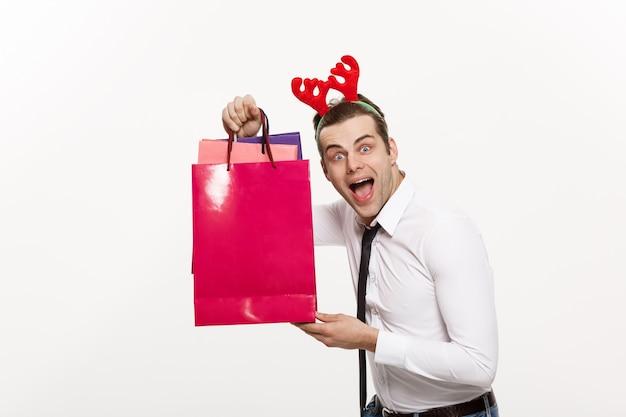 ハンサムなビジネスマンは、メリークリスマスと幸せな新年がトナカイヘアバンドを着て、サンタレッドの大きな袋を祝う。