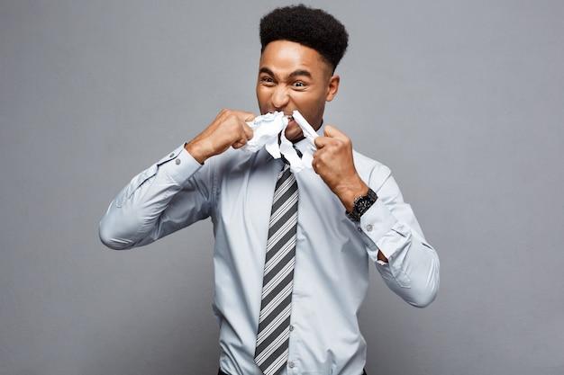 ビジネスコンセプト - 若い怒っているアフリカ系アメリカ人のビジネスマンは、ボール紙の紙を食べながら。失敗したプロジェクト