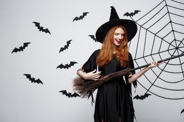 幸せなエレガントな魔女は、灰色の背景の上に箒のハロウィンパーティーで遊ぶことをお楽しみください。