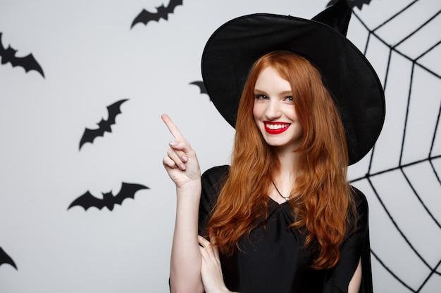 ハットハロウィーン魔女の指を指して、ダークグレーのスタジオの背景には、バットとスパイダーのウェブがあります。