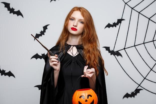 ハロウィーンを祝うためにオレンジのカボチャを保持している美しい白人の魔女の肖像画。