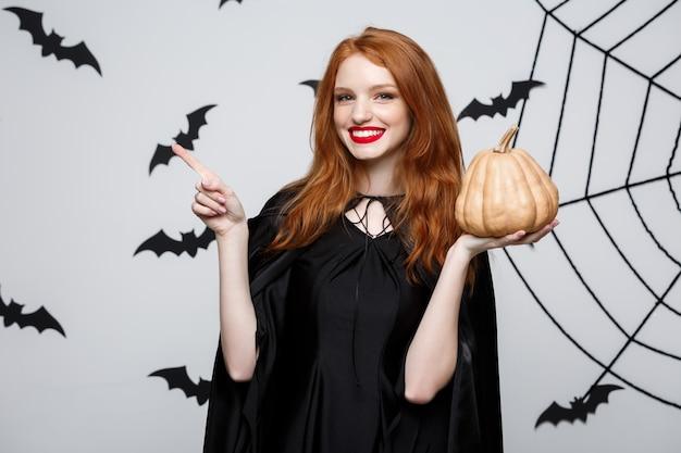 ハロウィンを祝うためにカボチャを保持している美しい白人の魔女の肖像画。