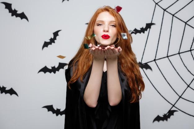 バットとスパイダーの背景の上にハロウィンパーティーを祝うための紙くずを吹くハッピーエレガントな魔女。