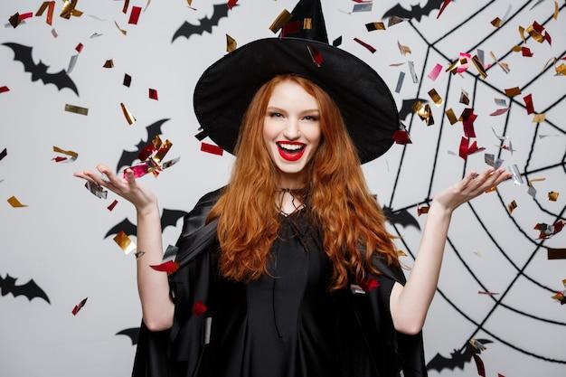 バットとスパイダーの背景の上にハロウィンパーティーを祝うための紙吹雪を投げるハッピーエレガントな魔女。