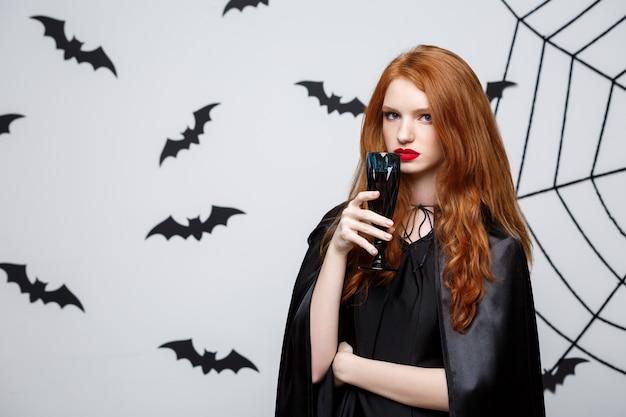 ハットハロウィン魔女、バットとスパイダーウェブと暗い灰色のスタジオの背景上に血なまぐさい赤ワインのガラスを保持します。