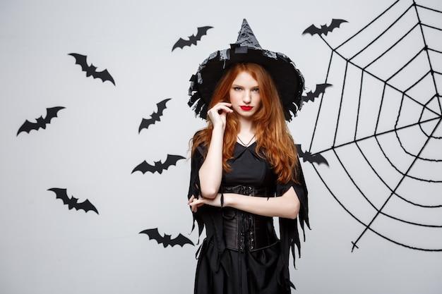 ハロウィン魔女、ダークグレースタジオの背景にバットとスパイダーウェブで深刻な表現でポーズをとっている。