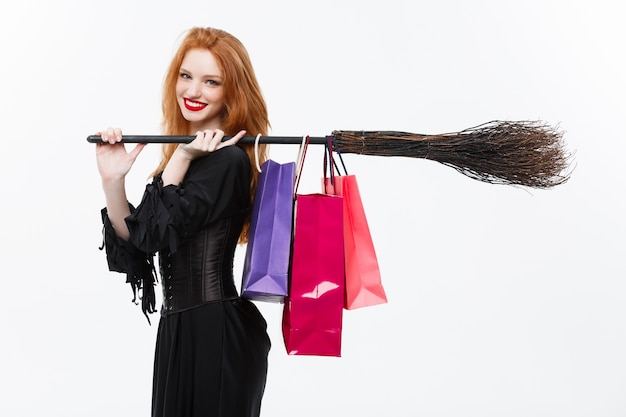 ハッピーハロウィン魔女は、笑顔と白い背景にカラフルなショッピングバッグを保持します。