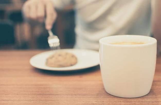 Человек с чашкой кофе и печенье в кафе, старинный цвет