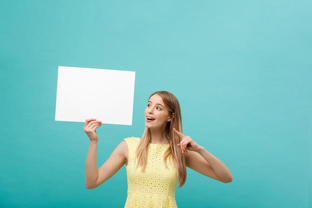 Молодая женщина в желтом платье указывая пальцем на стороне белый пустой доске. изолированные над синим