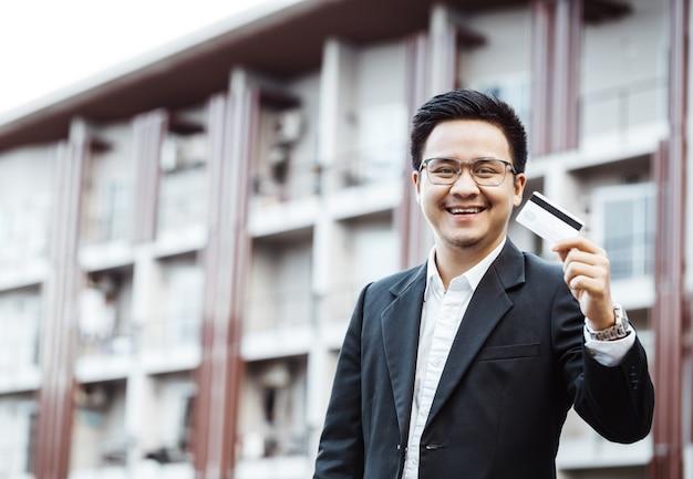 若いハンサムな男は、クレジットカードで携帯電話でオンラインショッピングを楽しむ。