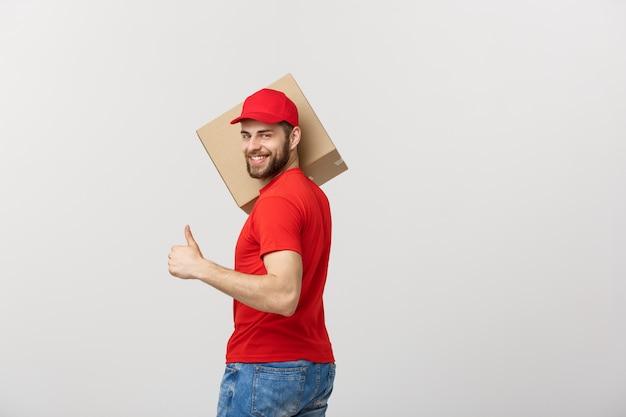 幸せな若いハンサムな配達人は、段ボール箱を保持し、彼の親指を上に見せる