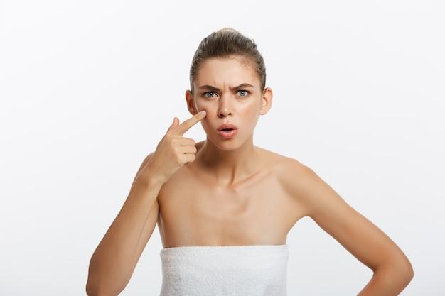Шокированная молодая полуобнаженная женщина осматривает ее лицо, глядя на зеркало