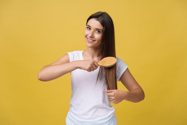 彼女の髪をくしゃく、カメラを見て、笑っている美しい若い女性の肖像画。