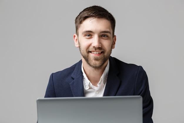 Бизнес-концепция - портрет красивый деловой человек, играя цифровой ноутбук с улыбающимся уверенным лицом. белый фон. копирование пространства.