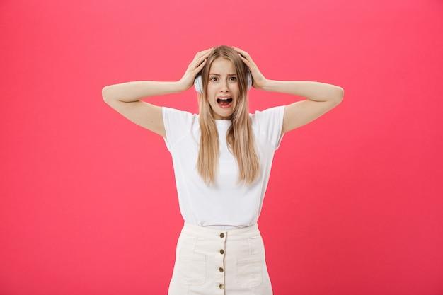 迷惑な大音量を無視して耳をカバーするコールセンターからの若い女性オペレーター