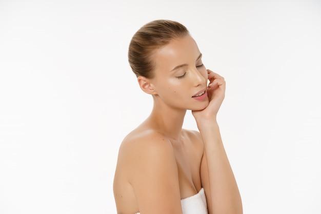 サイドビュー美しい女性が肌の顔を気遣う - 白で隔離されるスタジオでポーズをとる