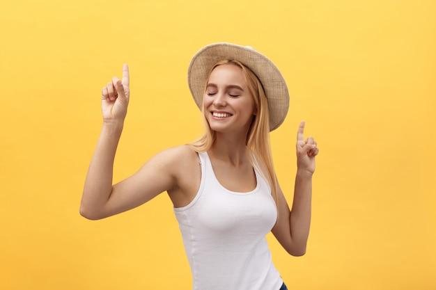 黄色の背景で隔離のスタジオで踊る若い美しい女性