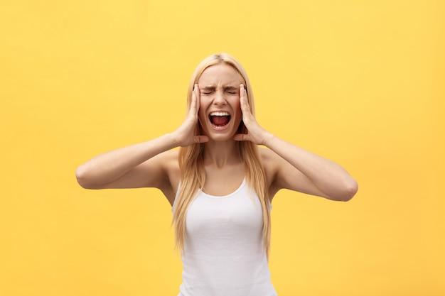 手で怒っているイライラした女性の肖像画は黄色の背景で隔離のカメラで叫び