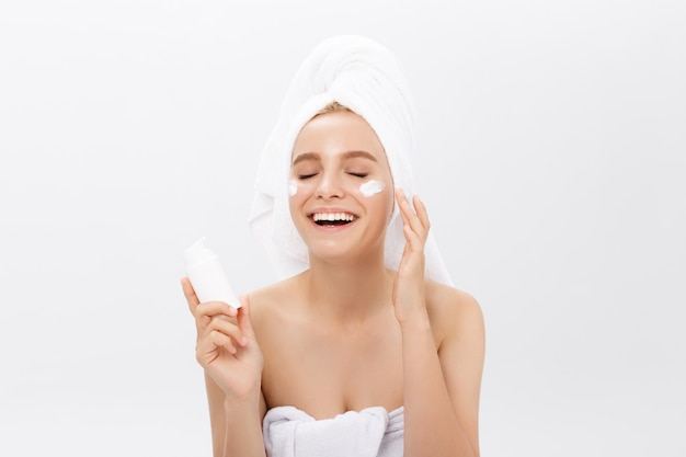 美しさ青少年スキンケアコンセプト - 美しい白人女性の顔の肖像画を保持しているクリームチューブ製品を提示します。