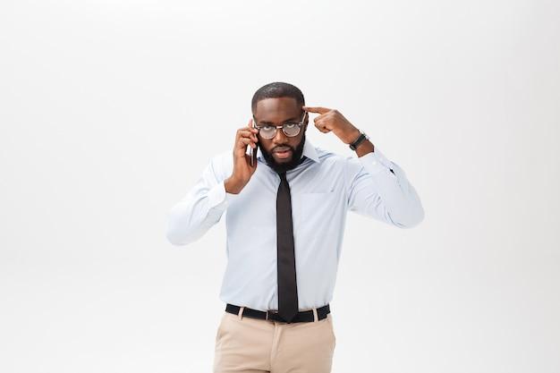 混乱している若いアフリカ人の肖像画は携帯電話で話していると白い背景で隔離された身振りで示す白いシャツに身を包んだ