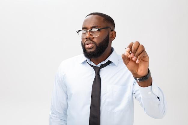 Молодой афроамериканец деловой человек, что-то писать на стеклянной доске с маркером