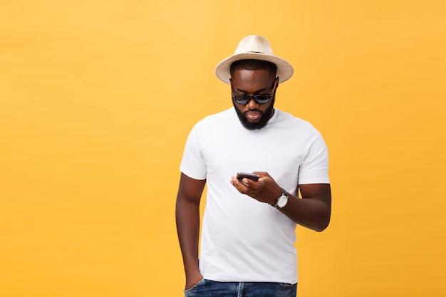 携帯電話のアプリケーションを使用して白いシャツで陽気なアフリカ系アメリカ人の男。